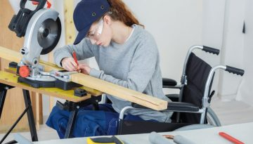 disabled female worker in wheelchair in a carpenters workshop